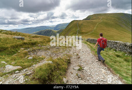 A hiker walking down from The Knott and on towards the summit of High Street in the English Lake District, UK. - Stock Image