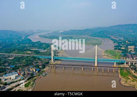 (190423) -- CHONGQING, April 23, 2019 (Xinhua) -- Aerial photo taken on April 23, 2019 shows the previous (Front) and the new Baishatuo Yangtze River railway bridge in Jiangjin of southwest China's Chongqing Municipality. The previous Baishatuo Yangtze River railway bridge, completed in 1959, will stop service after April 24. All trains will run on the new double decker steel truss cable stay railway bridge after that day. The new bridge has 4 tracks on the upper deck for passenger trains with a designed speed of 200 kilometers per hour and 2 tracks on the lower deck for cargo trains with the  - Stock Image