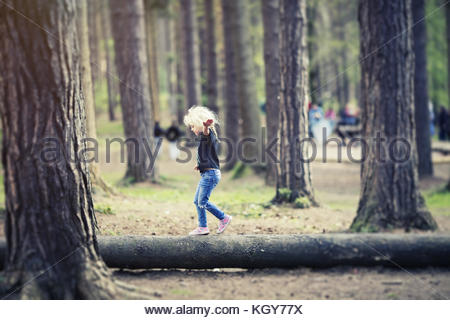 girl balancing on tree trunk - Stock Image