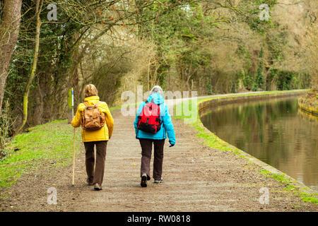 Two women wearing rucksack backpack walking along the Llangollen canal towpath near  Pontcysyllte North Wales UK - Stock Image