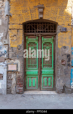 Old grunge green decorated painted door on dirty yellow painted stone wall, Old Cairo, Egypt - Stock Image