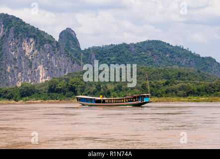 Traditional wooden tourists boat sailing on Mekong River trip. Pak Ou, Luang Prabang province, Laos, southeast Asia - Stock Image