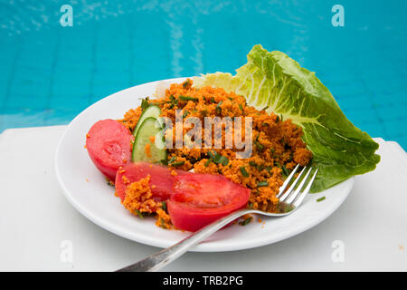 A traditional Turkish dish of Kisir, Bulgar wheat and red lentils served with a side salad. - Stock Image