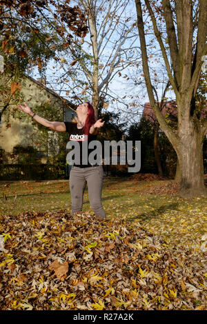 young female throwing leaves into the air in a park lenti zala county hungary - Stock Image