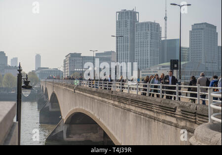 London, UK. 17th April, 2017. Extinction Rebellion Climate Change protesters continue a blockade of Waterloo Bridge to vehicle traffic but with a heavier police presence. Morning commuters cross the bridge walking to work in the City. Credit: Malcolm Park/Alamy Live News. - Stock Image