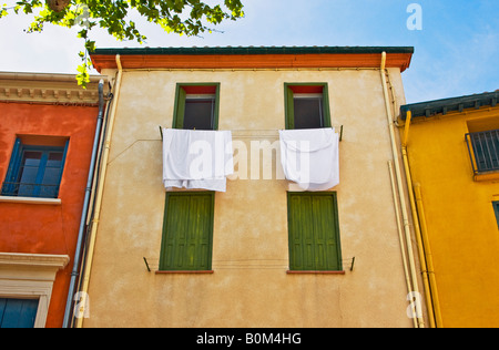 Laundry sheets hanging out of quaint building window Collioure France - Stock Image