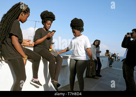 Young women friends tourists with African hairstyles & woman looking at mobile phone in the Alfama district of Lisbon Portugal Europe EU  KATHY DEWITT - Stock Image