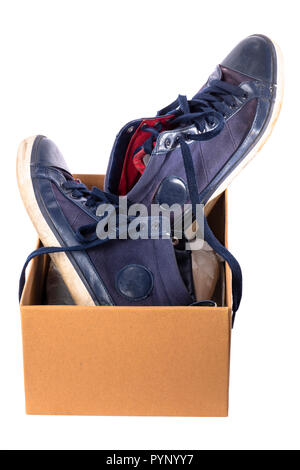 Old worn blue shoes, stuck in a cardboard box. Isolated on white background. - Stock Image