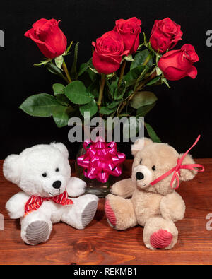 Two cute cuddly teddy bears with red roses in vase and pink bow on wooden table on dark background. Valentines, Mothers Day, Easter, Christmas, Weddin - Stock Image