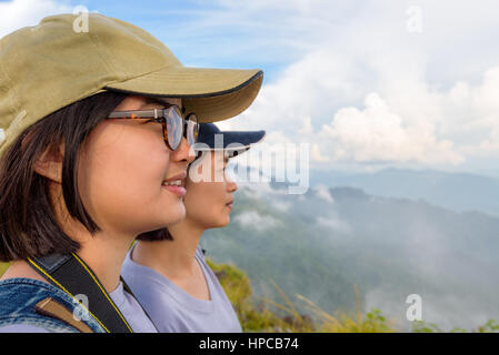 Face two young women hiker, mother and daughter smiling happily while looking beautiful landscape nature of mountain - Stock Image