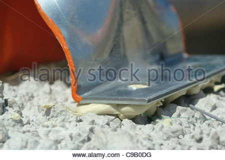 Metal bracket glued to cement concrete prior to drilling and bolting - Stock Image