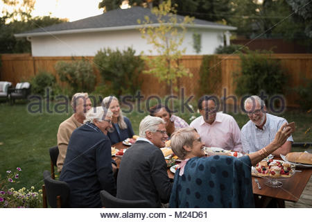 Senior friends taking selfie with camera phone at garden party lunch patio table - Stock Image