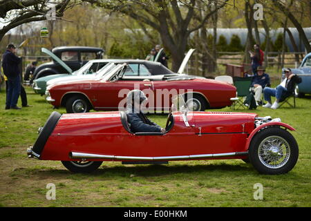 Floral Park, New York, U.S. 27th April, 2014. Owner STEVE KAPLAN, in driver's seat, is about to drive his red BRA CX3, a custom Beribo Replica Automobiles kit vehicle with three wheels, and registered by DMV as a 2009 Custom Motorcycle, at the 35th Annual Antique Auto Show at Queens Farm. Credit:  Ann E Parry/Alamy Live News - Stock Image