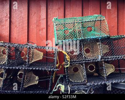 Empty crab pots or traps stacked up outside a red painted wooden shed in Valle, Norway. - Stock Image