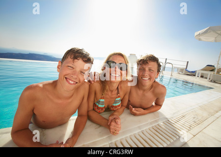 Family smiling in swimming pool - Stock Image