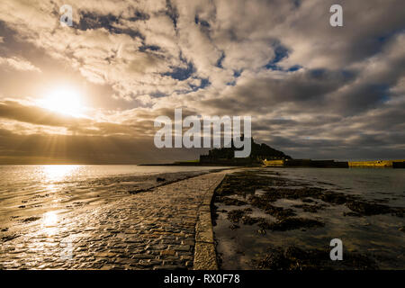 Sunburst over curving causeway at St Michael's Mount, Cornwall, UK - Stock Image