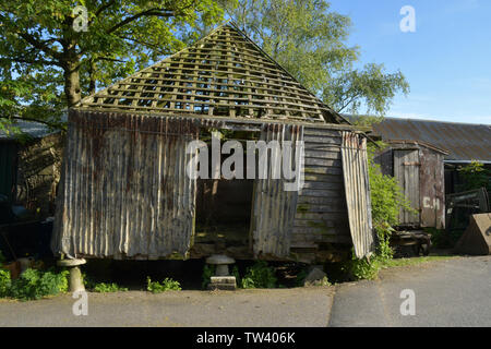 Old farm grain store on staddle stones.Wood and corrugated iron construction. Tiles removed for reuse and shed held together with rope.Old wheeled she - Stock Image
