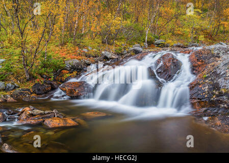 Waterfall in autumnal landscape - Stock Image