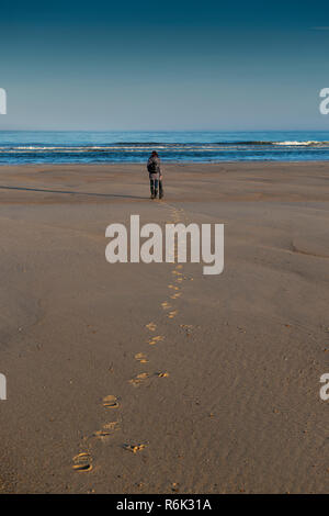 Young girl alone on the beach. - Stock Image