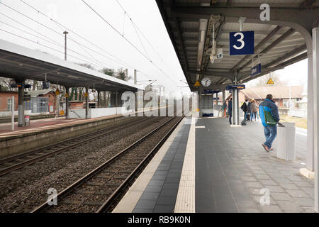 Gifhorn, Germany, December 29, 2018: Isenbüttel station of the small town of Gifhorn, few people on the platform, empty tracks with a dreary mood - Stock Image