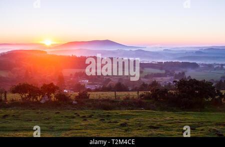 The sun sets over foggy farmland in Shropshire, England. - Stock Image