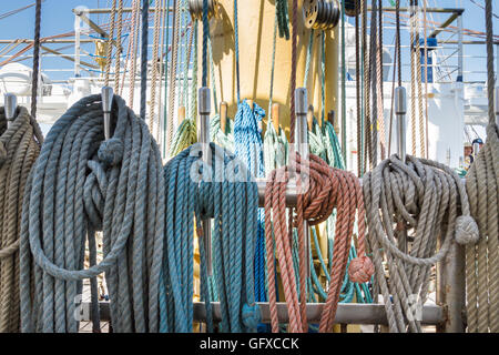 Detail of coiled, coloured lines (ropes) on a square-rigged ship called Mir (Peace) in Russian - Stock Image