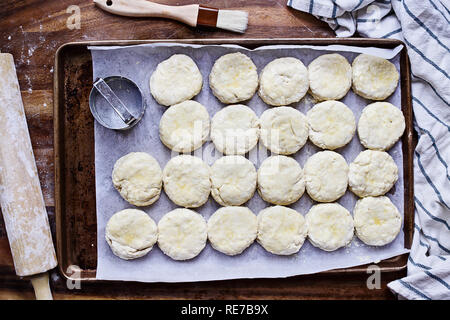 Raw buttermilk southern biscuit or scone dough from scratch with rolling pin and basting brush. Top view. - Stock Image