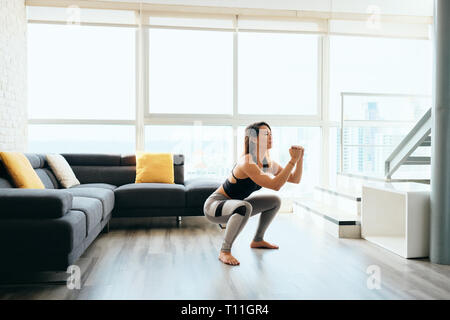 Fit young Pacific Islander woman training at home. Beautiful female athlete working out for wellbeing in domestic gym, training legs muscles with in a - Stock Image