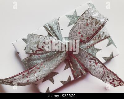 Christmas present decorated with a silver ribbon tied in a flamboyant bow - Stock Image