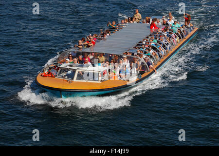 Fully occupied canal cruise boat southbound at full speed at Havnegade just before passing under Knippelsbro Bridge - Stock Image