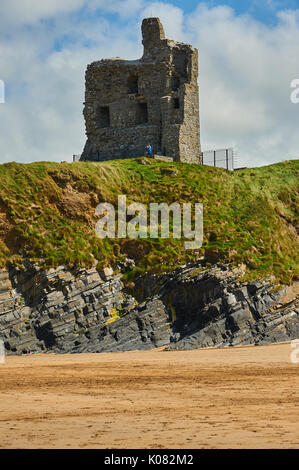 The ruins of Ballbunion castle in County Kerry over look the wide sandy beach and the Atlantic Ocean on a calm summer day. - Stock Image