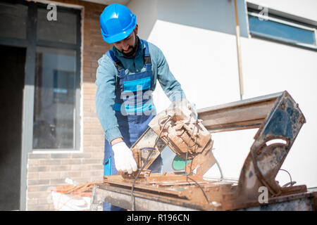 Builder in uniform cutting tiles with big electro saw on the construction site outdoors - Stock Image