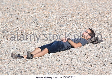 Worthing, UK. Sunday 8th July 2018. A man lays in the sun on the beach on a very warm morning in Worthing, on the South Coast. Credit: Geoff Smith / Alamy Live News. - Stock Image