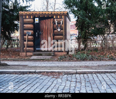 Heidelberger Platz, Wilmersdorf-Berlin.Utility box disguised as forester's shed - Paintwork of logs, ax and deer antlters - Stock Image