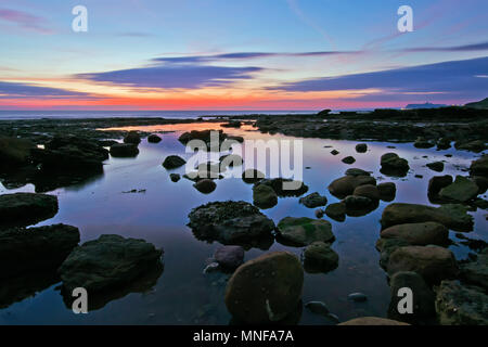 Coastal rock pools reflect the brilliant hues of dawn before sunrise at Crook Ness, near Scarborough. - Stock Image