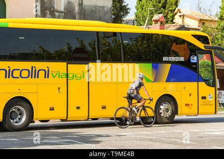 GARDA, LAKE GARDA, ITALY - SEPTEMBER 2018: Cyclist passing a tourist coach on the main road through the town of Garda on Lake Garda. The area is very  - Stock Image