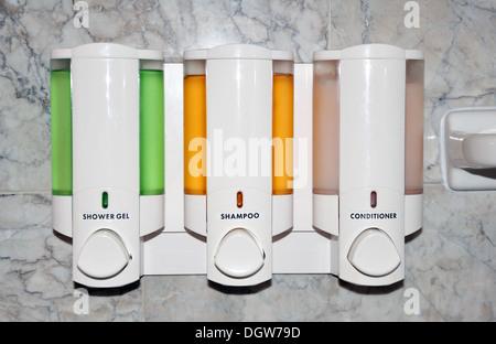 Shampoo and liquid soap dispenser in a hotel bathroom - Stock Image