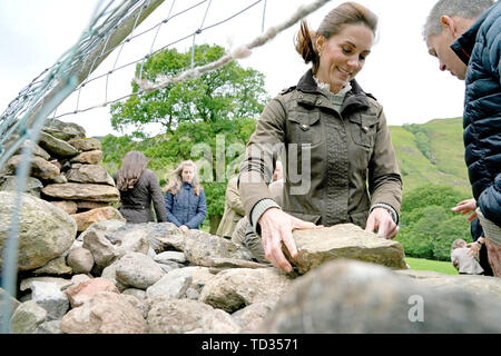 The Duchess of Cambridge takes part in the repair of a dry stone wall at Deepdale Hall Farm, a traditional fell sheep farm, in Patterdale, during a visit to Cumbria. - Stock Image