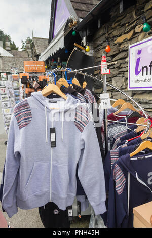 Smart grey hoodie and other clothing for sale outside Hawksheadtouristinfo gift shop and K70 Ooh-la-la clothing and interior decor shop, Hawkshead. - Stock Image