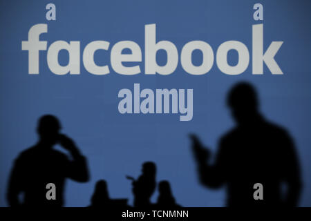 The Facebook logo is seen on an LED screen in the background while a silhouetted person uses a smartphone in the foreground (Editorial use only) - Stock Image