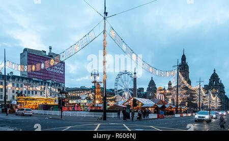 The Christmas Market in George Square in the centre of Glasgow. Big wheel, carousel, Christmas decorations, pedestrians and traffic, Scotland, UK. - Stock Image