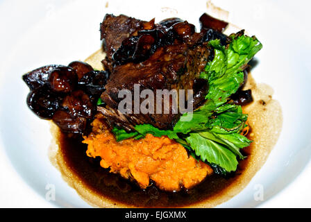 Boneless braised beef short rib button mushrooms mashed yams dinner entree arugula - Stock Image