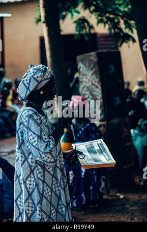 Black woman singing and dancing with a mic. Multi Ethnic music party to celebrate western and developing countries cooperation. Bamako, Mali. Africa - Stock Image