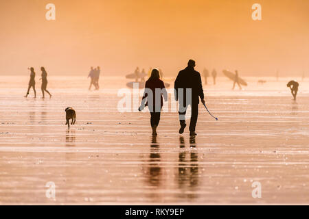People walking their dog on Fistral Beach in late evening sunlight. - Stock Image