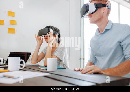 Young man and woman sitting at a table and using virtual reality goggles. Business team using virtual reality headset - Stock Image