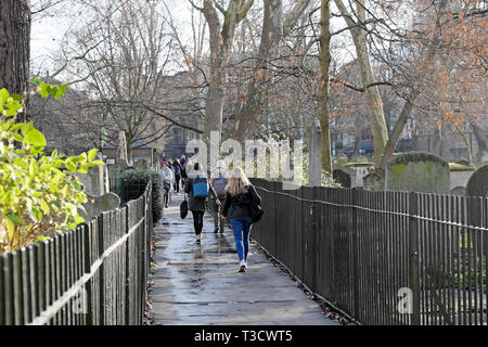 People walking to work and school along a path next to gravestones in Bunhill Fields Cemetery in early spring in London EC1 England UK  KATHY DEWITT - Stock Image