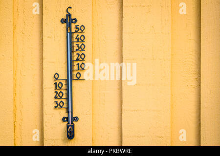 Weather thermometer hanging on a yellow wall on wooden planks - Stock Image