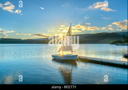 Lonely sailboat in the beautiful sunset with sun stars shines from sky and the surface of the lake is calm and peaceful when watching them - Stock Image