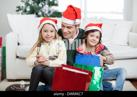 Siblings Sitting On Father's Lap With Christmas Presents - Stock Image