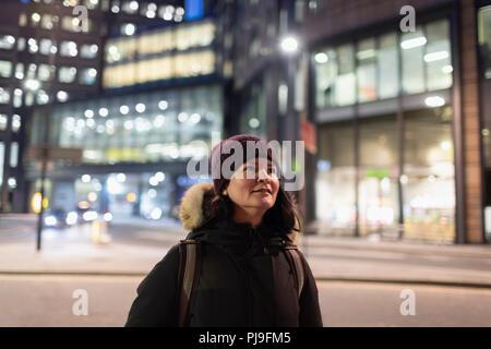 Woman in warm clothing walking on urban street at night - Stock Image